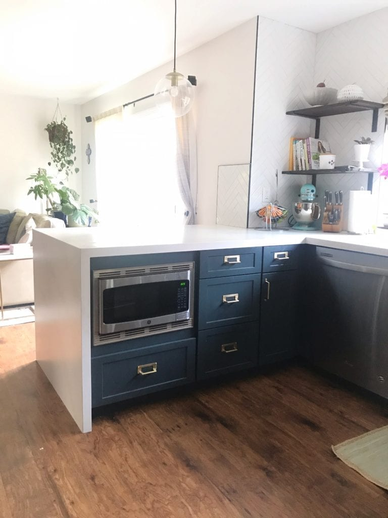 Before and After Kitchen Renovation with ideas and costs. See our farmhouse sink, herringbone backsplash with white subway tile and our DIY open shelving without changing our layout. Two-tone cabinets in woodgrain and blue. Including tips to get the most out of your budget. #kitcheremodel